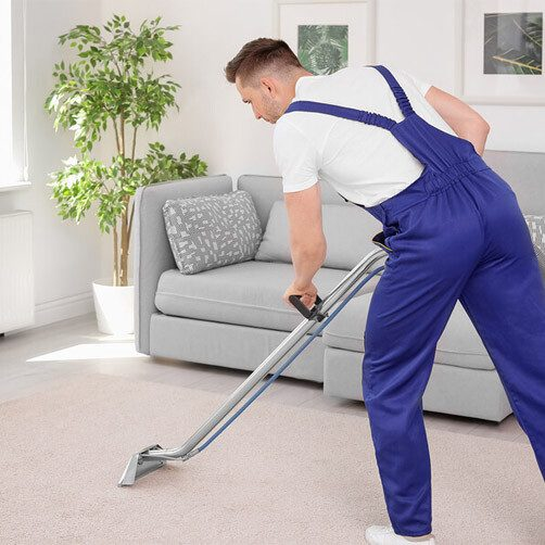 Service Technician Cleaning Carpet in Residence