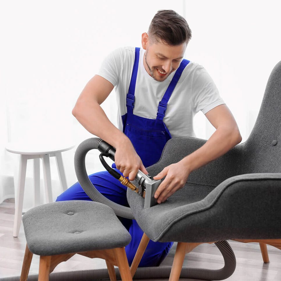 Cleaning Technician Performing Upholstery Cleaning Service On A Chair